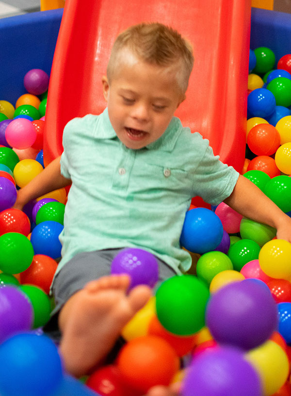 Little boy sliding into ball pit at Monkey Mouths
