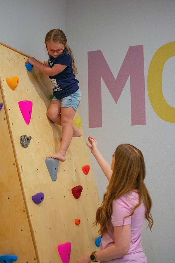 Little girl climbs bouldering wall as part of occupational therapy
